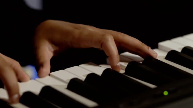 Male-hands-plays-melody-on-piano