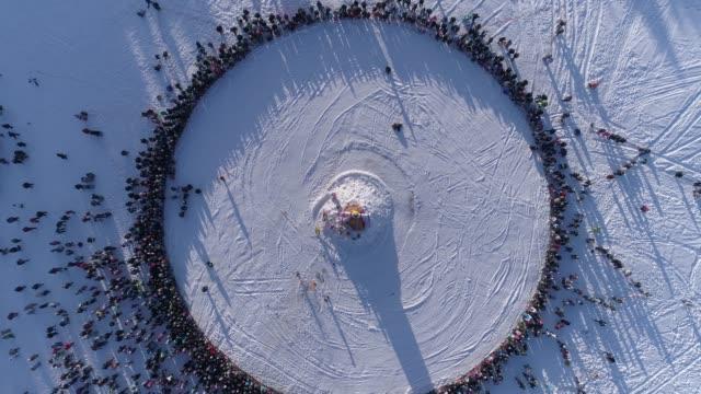 Círculo-de-personas-que-ver-quema-de-muñeco-durante-la-celebración-de-la-fiesta-tradicional-rusa-Maslenitsa-Material-de-archivo-Vista-aérea