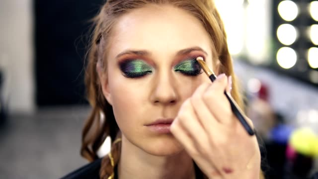 Make-up-stylist-finished-green-smokey-eyes-make-up-for-fair-hair-model-She-slowly-open-her-eyes-Front-view-Slow-motion