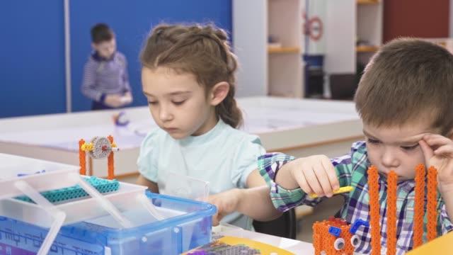 Niños-creando-robots-en-la-escuela-vástago-de-educación-Temprana-diy-innovación-para-el-desarrollo-concepto-de-la-tecnología-moderna-