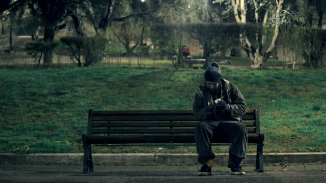 homeless-man-bench-counting-coins-in-a-city-park