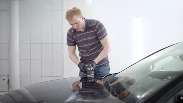 redhead-male-worker-is-processing-surface-of-car-by-polishing-machine-in-a-car-service-covering-by-protective-layer