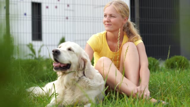 love-for-pets---a-young-blonde-woman-resting-with-her-dog-on-the-grass
