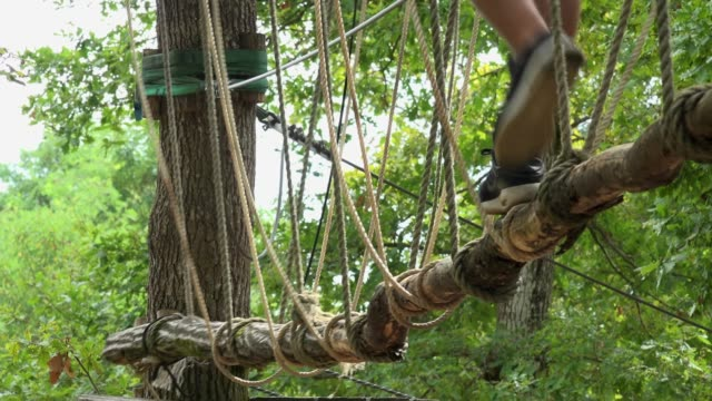 Child-passing-route-in-rope-park-Safety-equipment-carabiner-and-ropes-for-climbing-trees-in-extreme-park
