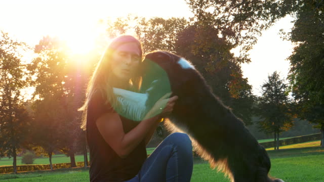Loving-female-pet-owner-petting-and-hugging-happy-dog-on-afternoon-walk-in-a-park-