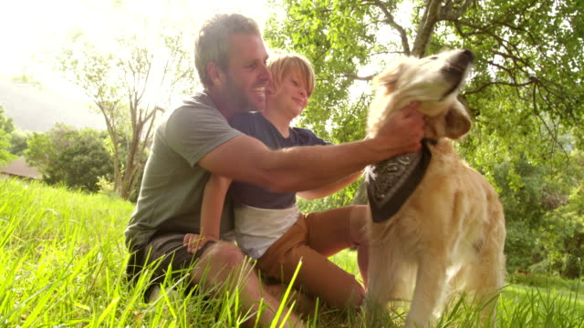 Dad-plays-with-his-cute-son-and-their-dog-outside