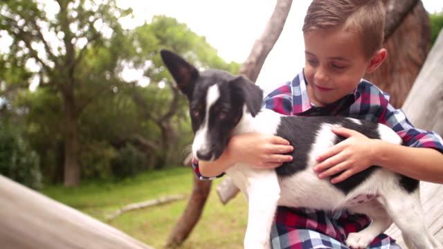 Closeup-cute-rascal-boy-gives-his-puppy-a-big-hug