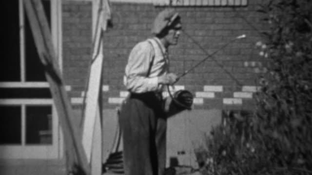 1935:-Man-spraying-pesticide-herbicide-chemicals-on-rose-bushes-