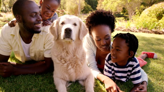 Cute-family-is-lying-in-the-grass-with-a-dog