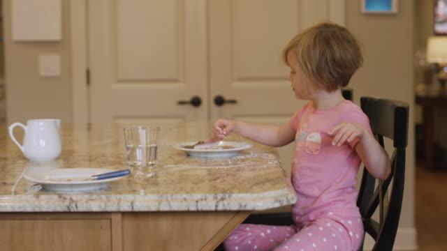 Una-niña-comiendo-azúcar-en-polvo-de-su-plato-con-los-dedos-con-su-perro-pidiendo-cerca