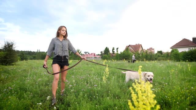 Attraktive-Frau-mit-dem-Hund-spazieren-gehen