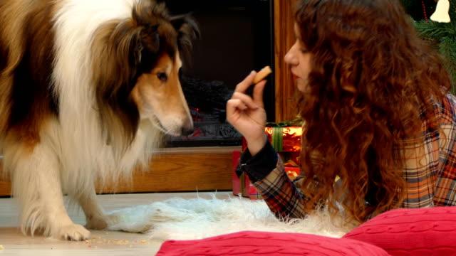 Girl-and-dog-eating-cookies-at-the-Christmas-tree
