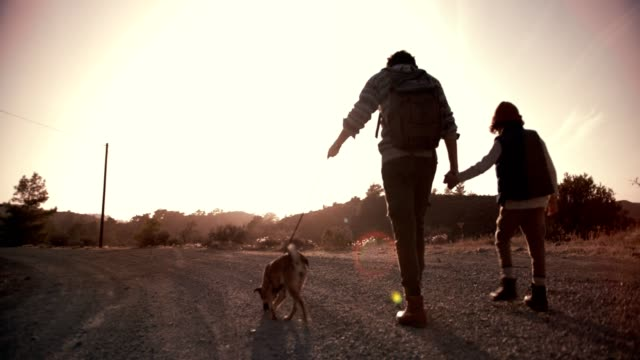 Young-father-and-son-walking-on-mountain-footpath-with-dog