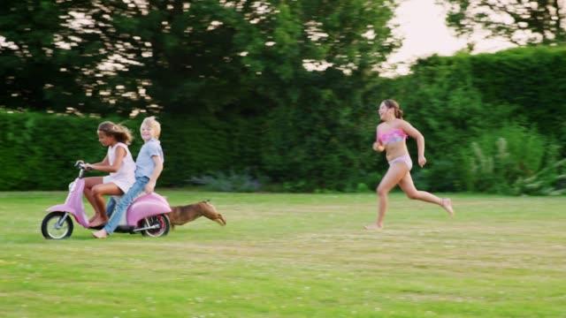 Adolescentes-niños-divirtiéndose-en-el-jardín-con-scooter-y-perro