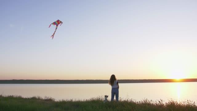Joven-mujer-feliz-y-het-perrito-con-volar-cometa-en-un-claro-en-el-ángulo-de-puesta-del-sol-bajo