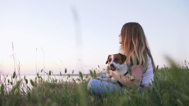 Joven-mujer-feliz-y-het-perrito-sentado-con-volar-cometa-en-un-claro-al-atardecer