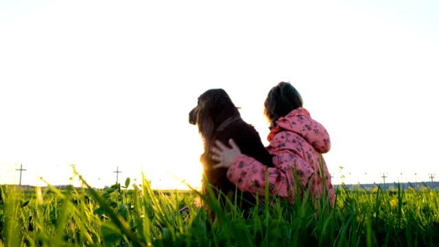 Mujer-abrazando-a-un-perro-en-la-puesta-de-sol-una-chica-joven-con-un-animal-doméstico-sentado-sobre-la-hierba-y-relajante-en-la-naturaleza