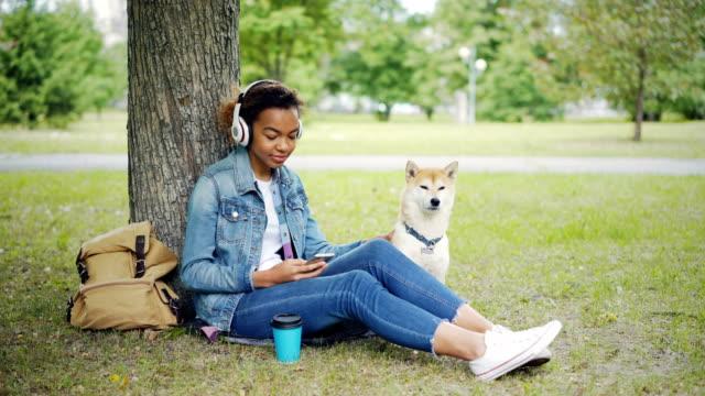 Moderne-afroamerikanische-Mädchen-hört-Musik-mit-Kopfhörern-und-mittels-Smartphone-entspannen-im-Stadtpark-mit-Hund-streicheln-und-liebkosen-das-Tier-
