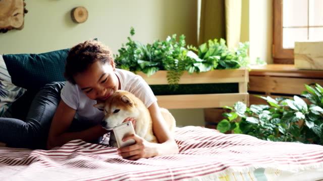 Sonriente-adolescente-de-raza-mezclada-es-tomar-selfie-con-cachorro-entonces-hablando-con-él-y-muestra-fotos-en-la-pantalla-del-smartphone-acostado-en-cama-en-casa-Concepto-de-tecnología-y-los-animales-domésticos-