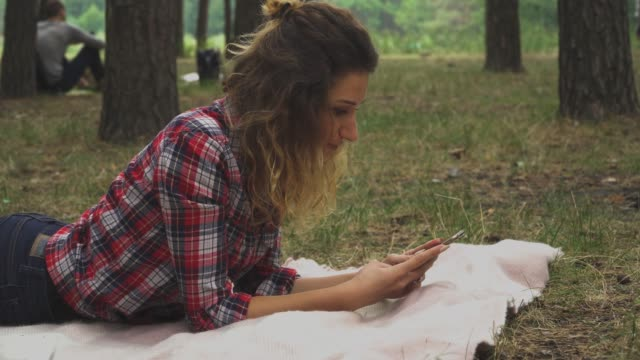 Curly-woman-is-laying-at-the-blanket-in-the-park