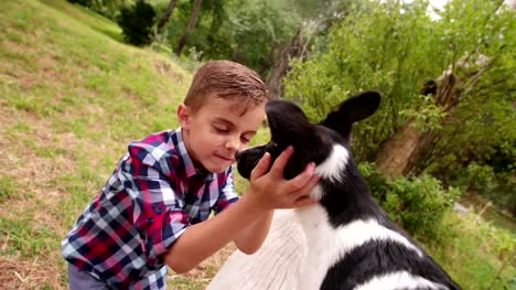 Little-boy-hugging-and-stroking-his-puppy-dog-in-park