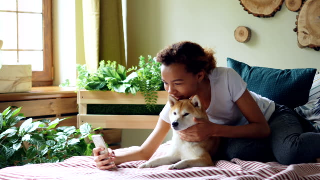 Pretty-girl-proud-dog-owner-is-making-video-call-and-caressing-her-purebred-dog-lying-on-bed-at-home-young-woman-is-talking-and-showing-animal-to-interlocutor-