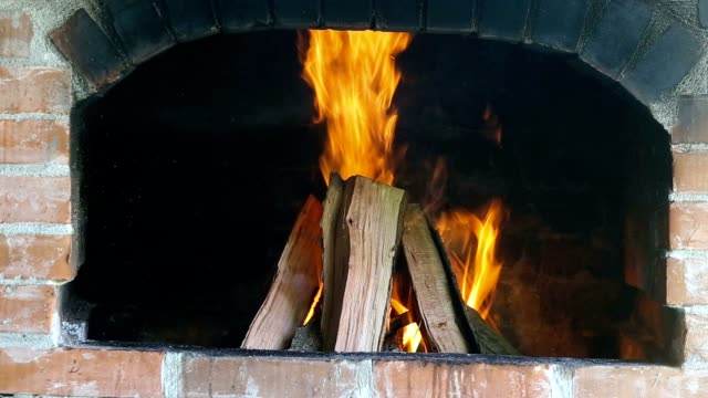 Wood-fire-in-a-red-brick-fireplace