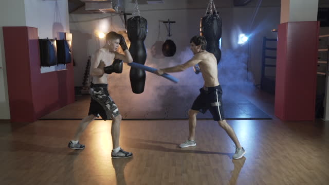 Training-sposstrstmenov-in-the-boxing-hall-Preparation-of-the-master-of-sports-for-battle-with-the-champion-The-trainer-and-the-boxer-work-out-blows-The-concept-of-sport-strength-boxing