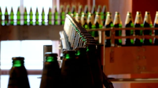 Large-number-of-glass-bottles-with-beer-are-moving-along-the-conveyor-Low-alcohol-production-Drinks-are-ready-to-eat-Factory-equipment-at-work-The-finished-product-moves-to-another-stage-Factory-automation-
