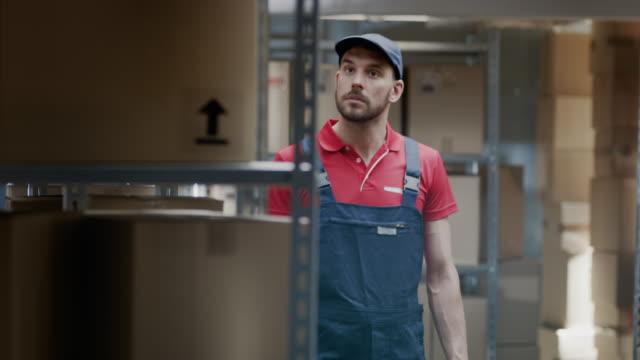 Trabajador-camina-a-través-de-almacén-control-de-Stock-en-el-lineal-de-cajas-de-cartón-de-pie-