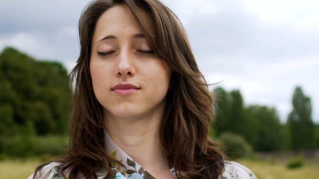Junge-Frau-steht-mit-im-Freien-geschlossenen-Augen-Gefühl-sich-selbst-und-die-Welt-um-sich-herum