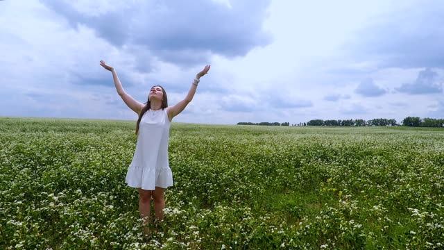 Woman-stands-in-field-hands-held-high-female-feels-nature-sense-wind-sun-on-skin