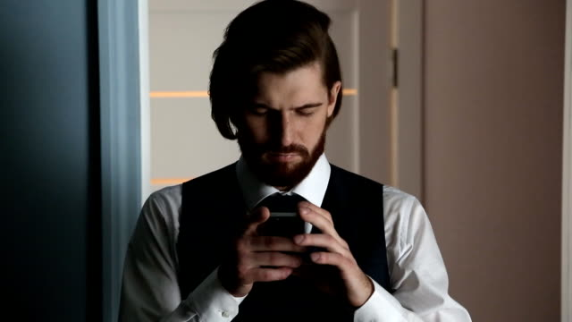 Bearded-handsome-young-man-using-his-smartphone-