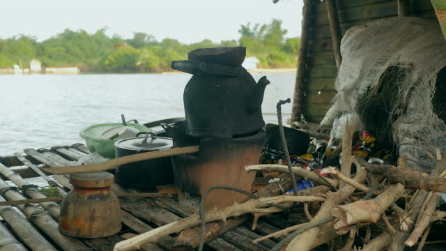 close-up-of-an-old-fashioned-kettle-over-traditional-household-cook-stove-heated-by-charcoal-in-a-houseboat
