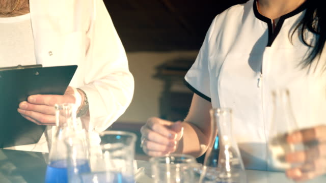 two-doctors-in-eyglasses-are-experimenting-with-test-tubes-with-chemicals-at-a-table-in-the-laboratory-on-a-black-background-