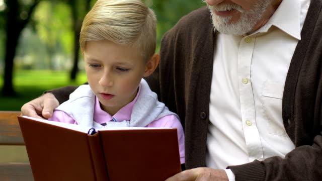 Kleine-Jungen-und-Großvater-Buch-zu-lesen-Relaxen-auf-der-Bank-im-Park-Bildung