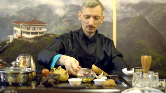 Tea-ceremony-Master-man-pours-green-tea-from-a-glass-teapot-into-a-white-mug