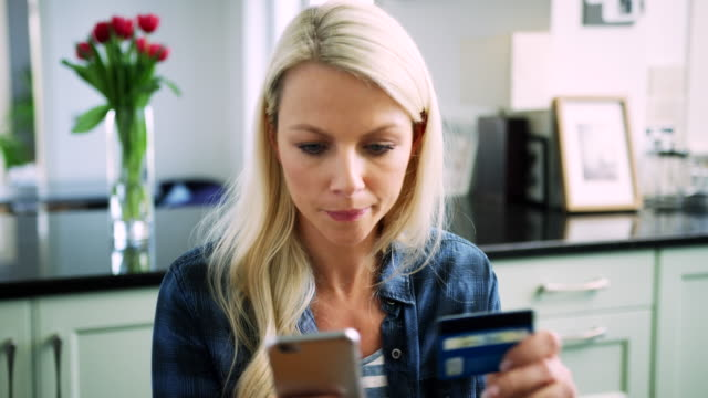 Beautiful-Blond-Woman-Typing-Credit-Card-Details-Into-Smart-Phone