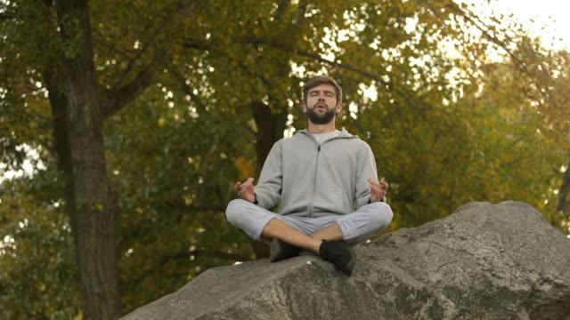 Male-doing-yoga-outdoors-lotus-pose-meditating-in-wild-harmony-and-balance