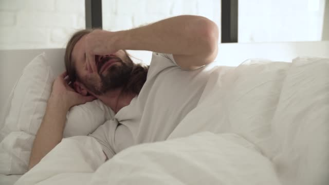 Man-Sleeping-Waking-Up-In-Morning-In-Bed-With-White-Linens