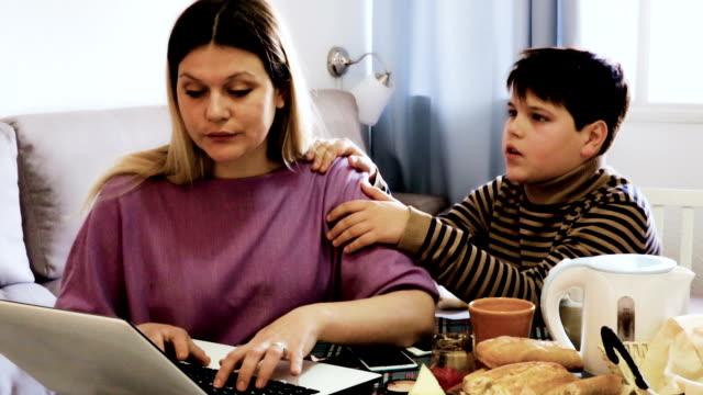 mujer-trabajando-y-chico-triste-de-pie-cerca-de-la-mesa-en-casa