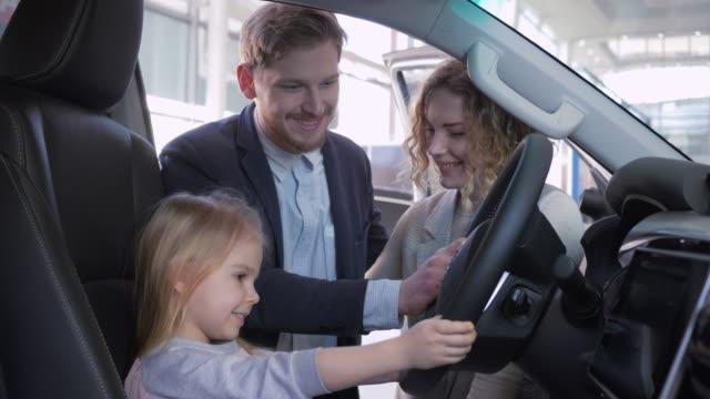 comprar-coche-familiar-niña-pequeña-detrás-de-la-rueda-de-auto-nuevo-junto-con-los-padres-mientras-compra-automóviles-en-el-showroom-de-cerca