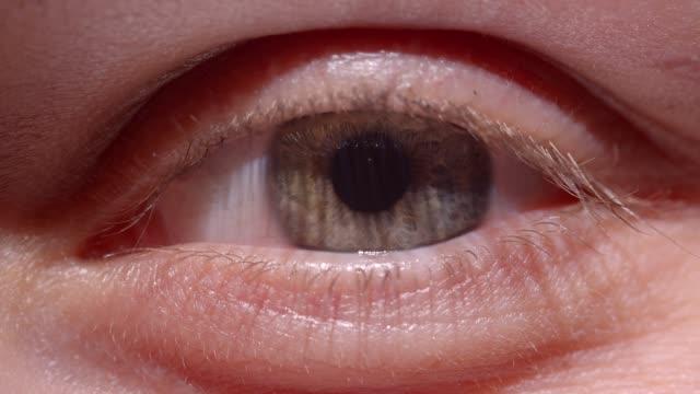 Brote-de-primer-plano-de-ensanchamiento-de-ojos-verdosos-y-encogiendo-rápidamente-la-pupila-