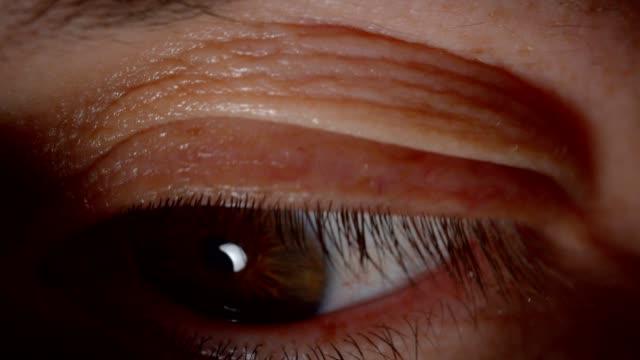 Sesión-de-primer-plano-de-una-persona-caucásica-con-los-ojos-marrones-parpadeando-y-mirando-tranquilamente-a-la-cámara-en-la-oscuridad-