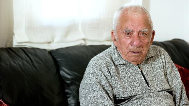 Anciano-deprimido-triste-sentarse-en-el-sofá-mirando-la-cámara