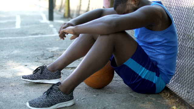 Sad-African-American-basketball-player-sitting-on-the-ground-lack-of-motivation