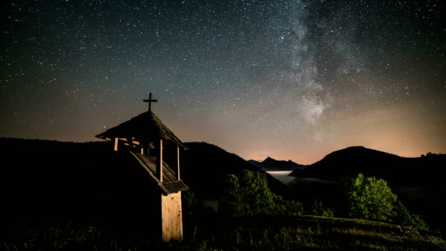 Stars-with-milky-way-galaxy-moving-over-wooden-belfry-in-mountains-and-foggy-valley-rural-country-Dolly-shot-time-lapse-starry-night-sky