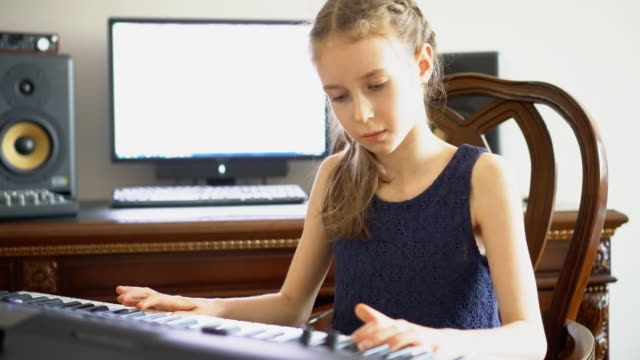 Little-girl-rehearsing-a-song-in-home-music-studio-