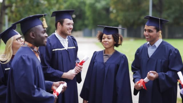 happy-students-in-mortar-boards-with-diplomas