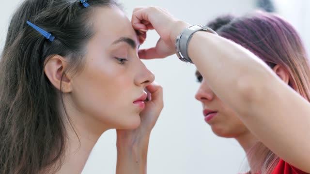 Primer-plano-profesional-make-up-artist-con-ojos-maquillaje-en-la-cara-del-modelo-de-mujer-joven